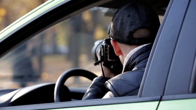 Spy is watching two women criminals from the car, taking pictures of how women exchange packages Spy is watching two women criminals from the car, taking pictures of how women exchange packages. detective stock videos & royalty-free footage