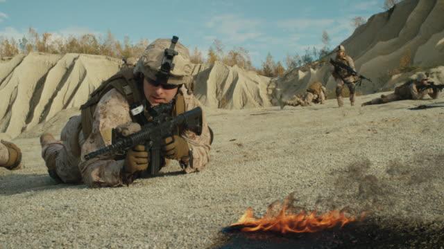 stockvideo's en b-roll-footage met ploeg van volledig uitgeruste en gewapende soldaten kruipen tijdens militaire operatie in de woestijn. - zeemacht