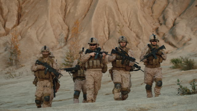 Squad of Fully Equipped and Armed Soldiers Walking Forward towards Camera in Desert Environment. Slow Motion. video