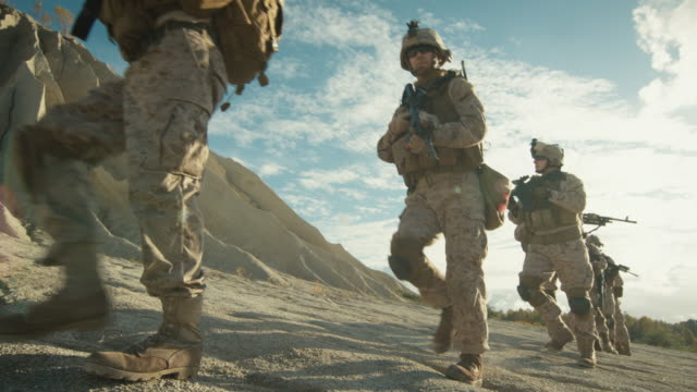 Squad of Fully Equipped and Armed Soldiers Walking in Single File in the Desert. Slow Motion. Squad of Fully Equipped and Armed Soldiers Walking in Single File in the Desert. Slow Motion. Shot on RED EPIC 4K (UHD). army stock videos & royalty-free footage