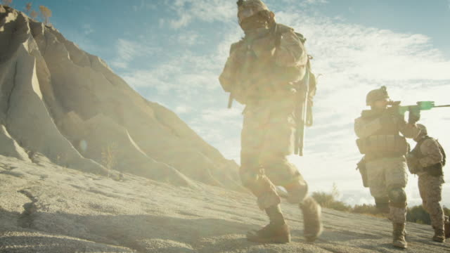 Squad of Fully Equipped and Armed Soldiers Walking in Single File in the Desert. Slow Motion. - vídeo