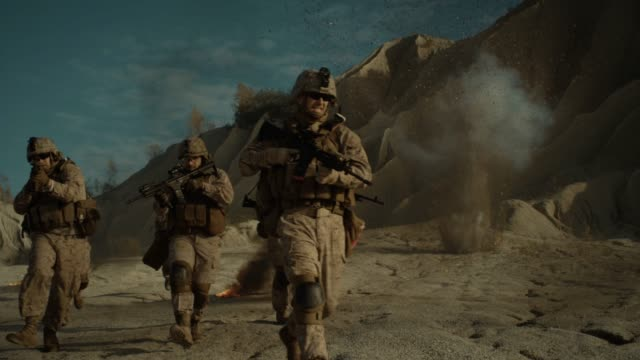 squad of fully equipped, armed soldiers being attacked and bombed during combat mission in the desert region. heroic action of brave soldiers in the face of deadly danger. enemy fire - wojna filmów i materiałów b-roll