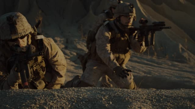 vídeos de stock e filmes b-roll de squad of fully equipped, armed soldiers on a reconnaissance mission in the desert country. team crawls into position of best enemy visibility. - fuzileiro naval