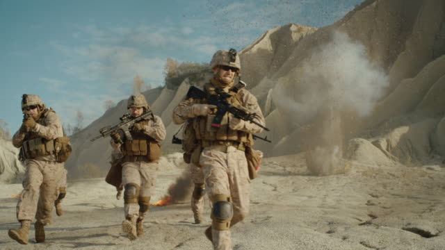 Squad of Fully Equipped, Armed Soldiers Running and Attacking During Military Operation in the Desert. Slow Motion.