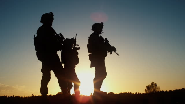 Squad of Three Fully Equipped and Armed Soldiers Standing in Desert Environment in Sunset Light. Slow Motion. - vídeo