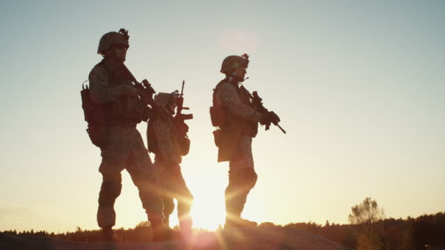 Squad of Three Fully Equipped and Armed Soldiers Standing on Hill in Desert Environment in Sunset Light. Slow Motion. - vídeo