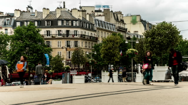 Square crowded by people with suitcases walking around during day, time-lapse video
