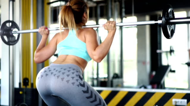Squat training. Closeup rear view of a sexy and partially unrecognizable mid 20's woman doing squats in front of a gym mirror. 4k brightly lit stock videos & royalty-free footage