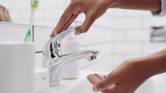 Squeaky clean and sanitized 4k footage of a woman washing her hands in the bathroom sink at home faucet stock videos & royalty-free footage