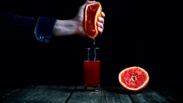 squeeze juice from grapefruit by hand on a black background - сжимать стоковые видео и кадры b-roll