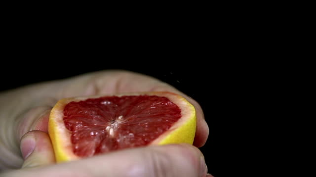 HD SLOW: Squeezing a grapefruit which spurts its juices video