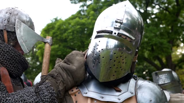 A squire helping a knight with his armor Medieval warrior with body armor on a traditional festival with a squire getting dressed. knight person stock videos & royalty-free footage