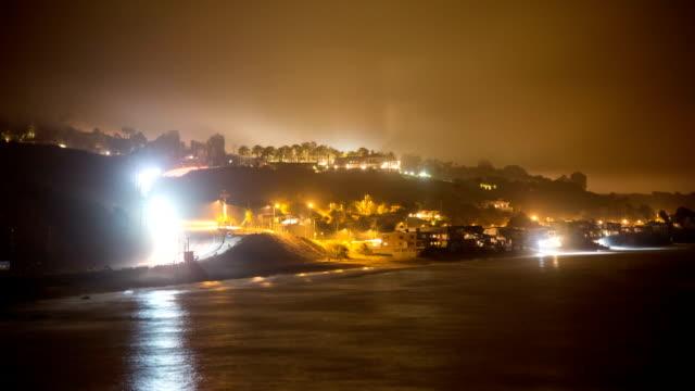 stockvideo's en b-roll-footage met s-vormige verkeerspatronen langs de kust van californië.  mist en lichtvervuiling. timelapse. - s