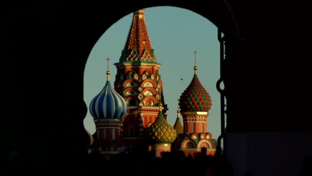 St Basil's Cathedral in Moscow Red Square Kremlin in frame through dark gate. City crowd of people in blur. Moscow Red Square and Kremlin tower as symbol of Russia power and President of Russia. Slow motion bird flies against background video