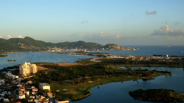 st maartin aerial v1 flying low over lagoon panning with golf course views at sunset. - saint martin caraibi video stock e b–roll