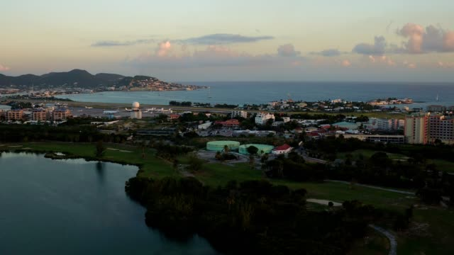 st maartin aerial v4 flying low over golf course panning with maho beach views. - saint martin caraibi video stock e b–roll