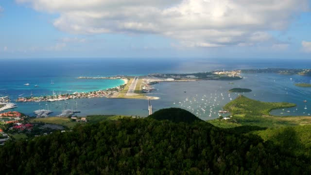 st maartin aerial v52 flying low over tall hillsides sideways with views of airport and runway. - saint martin caraibi video stock e b–roll