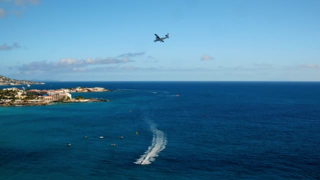 st maartin aerial v56 flying low over bay panning with views of simpson bay and small plane landing. - saint martin caraibi video stock e b–roll