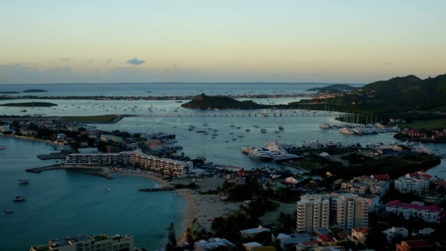 st maartin aerial v65 flying low over simpson bay town panning at sunset. - saint martin caraibi video stock e b–roll