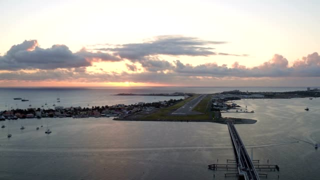 st maartin aerial v67 flying low backwards over simpson bay lagoon with views at sunset. - saint martin caraibi video stock e b–roll