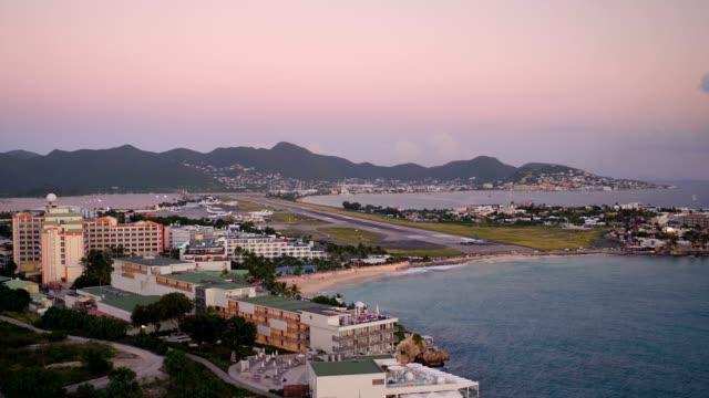 st maartin aerial v7 flying low backwards with maho beach views. - saint martin caraibi video stock e b–roll