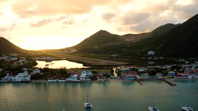 st maartin aerial v71 flying low over grand case bay panning with town views at sunrise. - saint martin caraibi video stock e b–roll