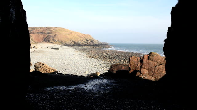 St Ninian's Cave Emerging from St Ninian's Cave on the shoreline at Physgill in Dumfries and Galloway, Southern Scotland.  Tradition holds that the cave, was the hermitage, or hideaway, of St Ninian. dumfries and galloway stock videos & royalty-free footage