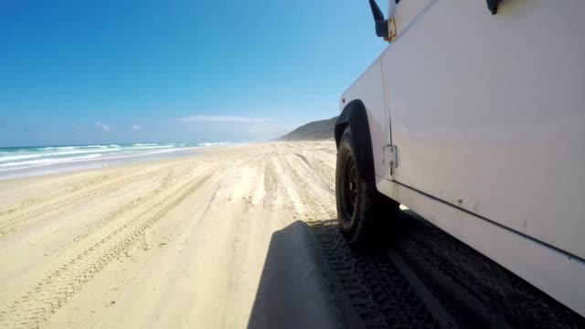 Stabilized action low angle footage of an old four-wheel drive off-road vehicle driving on famous Seventy Five Mile Beach (75 Mile Beach) on Fraser Island off the coast of Queensland, Australia. Stabilized action low angle footage of an old four-wheel drive off-road vehicle driving on famous Seventy Five Mile Beach (75 Mile Beach) on Fraser Island off the coast of Queensland, Australia. low angle view stock videos & royalty-free footage