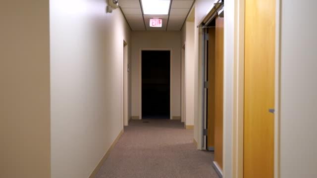 стабилизированная снимок перемещение вниз коридор в темный зал и точения - empty room стоковые видео и кадры b-roll