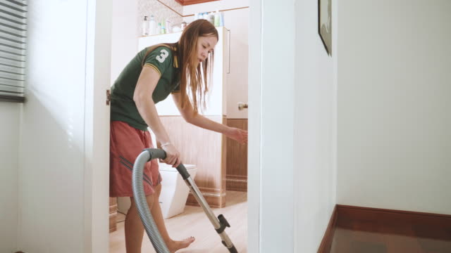 Stabilized Shot Of Women Using Vacuum Cleaner Cleaning On The Ground video