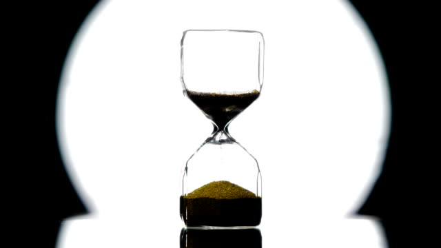 Stable Time Costs Hourglass in Style Noir.Golden sand is strewed against the background of a bright round beam of a spotlight on a black. Filmed at a speed of 240fps hourglass stock videos & royalty-free footage