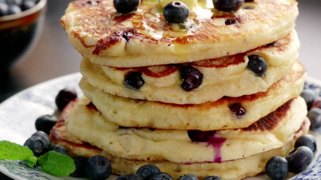 vídeos de stock e filmes b-roll de stack of blueberry pancakes with butter and maple syrup - vacínio