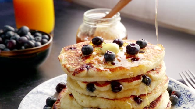 stack of blueberry pancakes with butter and maple syrup - pancake video stock e b–roll