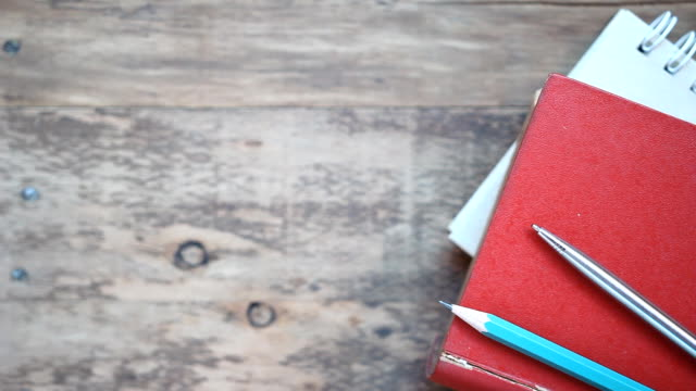 stack of book with pen on wood table background video