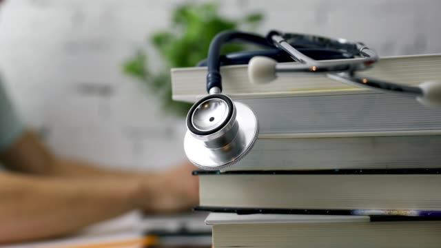 stack of books with stethoscope and medical student working on laptop