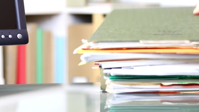 Stack of files, documents being piled onto office desk. video