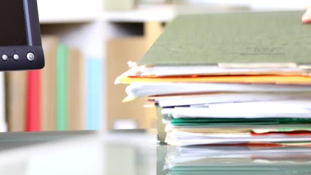 vídeos de stock, filmes e b-roll de pilha de arquivos, documentos, sendo empilhados em mesa de escritório. - rh