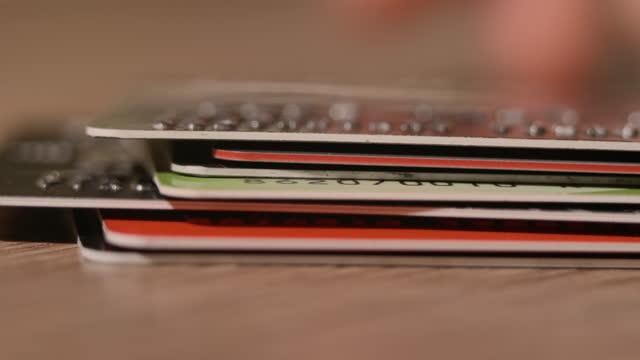 stapel von bunten kreditkarten, close up view mit selektivem fokus. geld auf bankkonten. kreditkarten liegen auf dem tisch. bargeldlose zahlungen. online-shopping kaufen. consumerism shopper consumer - viele gegenstände stock-videos und b-roll-filmmaterial