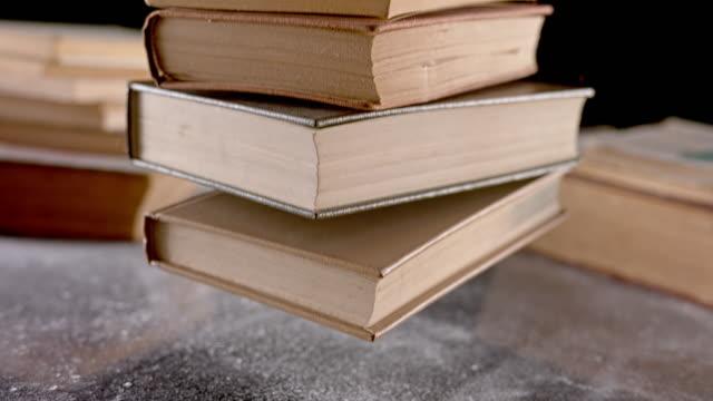 stockvideo's en b-roll-footage met slo mo stapel van oude boeken die op een lijst vallen - literatuur