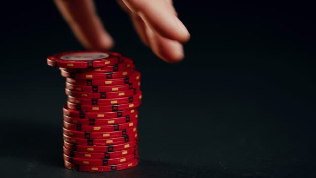 A stack of red poker chips slides in on a black background. At the end the hand takes them away.