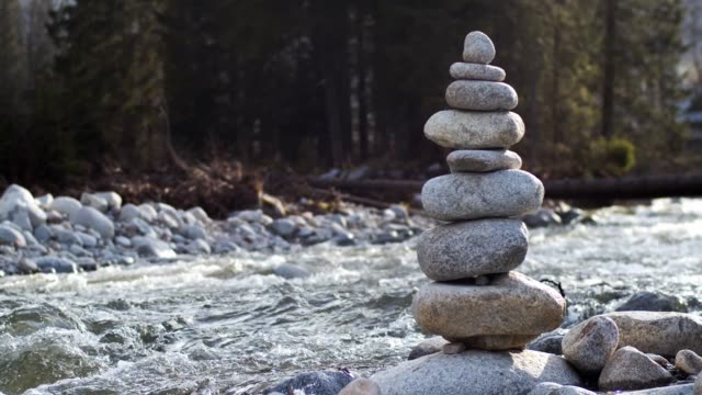 Stack of stones standing on riverbank.