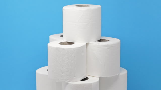 Stack of toilet paper rolls rotating against a blue background