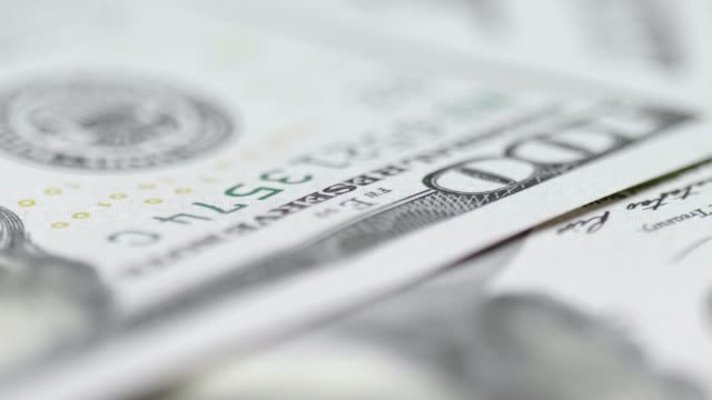 Stack of US one hundred dollar bills A scattered stack of US one hundred dollar bills rotate on a table top. financial planning stock videos & royalty-free footage