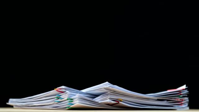stack sovraccarico di carta report documento con graffetta colorata su sfondo nero, filmati di concetto aziendale senza carta utilizzati - 4k stop motion. - catasta video stock e b–roll