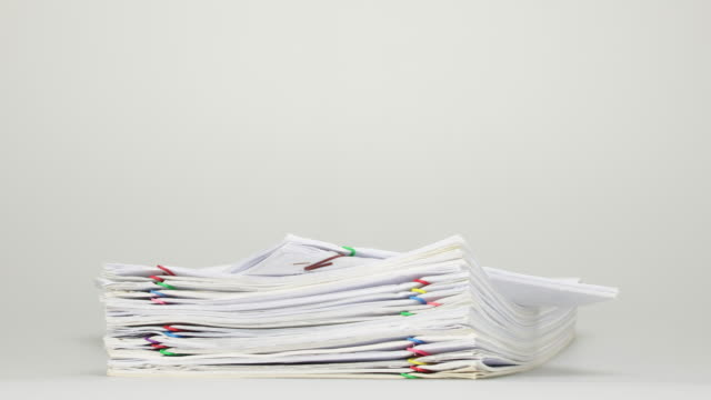 Stack overload receipt and report on white table time lapse Stack overload document of receipt and report with colorful paperclip place on white table time lapse. heap stock videos & royalty-free footage