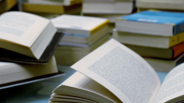 stacked books opened on a table - tracking shot video