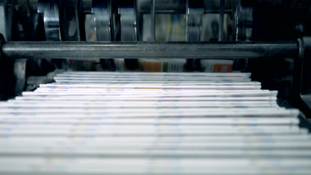 Stacked newspaper on automated conveyor, typography facility. Stacked newspaper on automated conveyor, typography facility. 4K printmaking technique stock videos & royalty-free footage