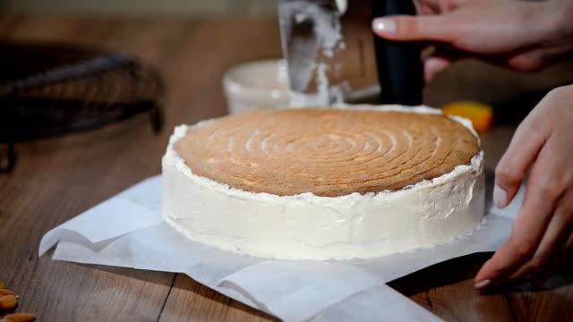 Stacking cake layers. Making torte with buttercream filling video