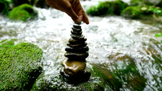 stacking zen stones in nature - pietra roccia video stock e b–roll