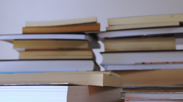 Stacks of books time lapse Stacks of books on wooden table ,time lapse from one book in focus to stacks of different books textbook stock videos & royalty-free footage